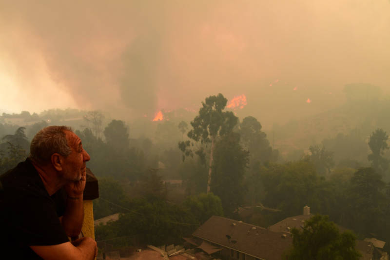 Local resident Ruben Garibyan watches the approach of flames from the La Tuna Fire from his balcony in the Shadow Hills neighborhood of Los Angeles on Sept. 2, 2017.