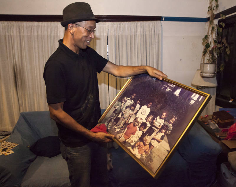 "Musashi ""Moose"" Lethridge holds a family photo of himself (top center) and his sister (bottom center) as children along with several other friends who grew up in their neighborhood in Oakland."