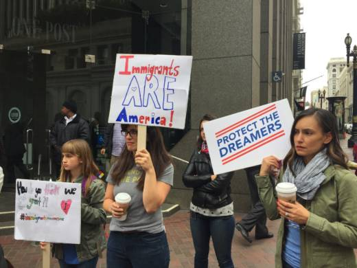 Jasmine Mongue, Kim Wilson and Caitlin Lang (L-R) hold signs at a pro-DACA rally in San Francisco's Financial District on Tuesday, August 15, 2017. It was the fifth anniversary of the program which provides work permits and protection from deportation for children brought to the country illegally.