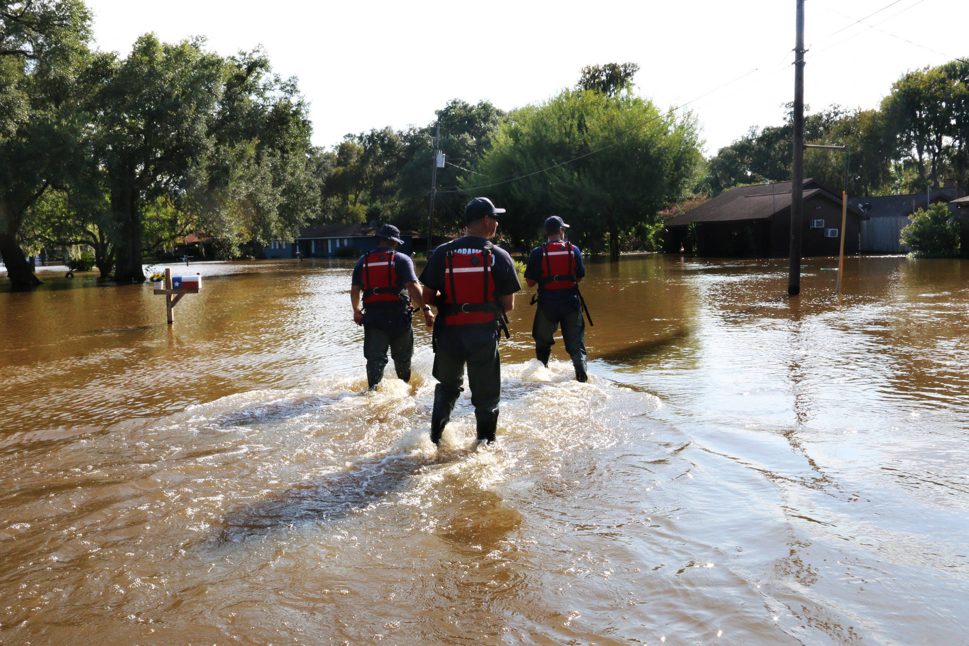 (From Left) Scott Lewis, Mike Wolfe and Dave Lauchner, members of Urban Search and Rescue California Task Force 7 and the Sacramento Fire Department, walk through Richwood, Texas, on Sept. 3, 2017. Richwood is one of many rural communities that continue to see major flooding over a week after Hurricane Harvey hit Texas. Alex Emslie/KQED