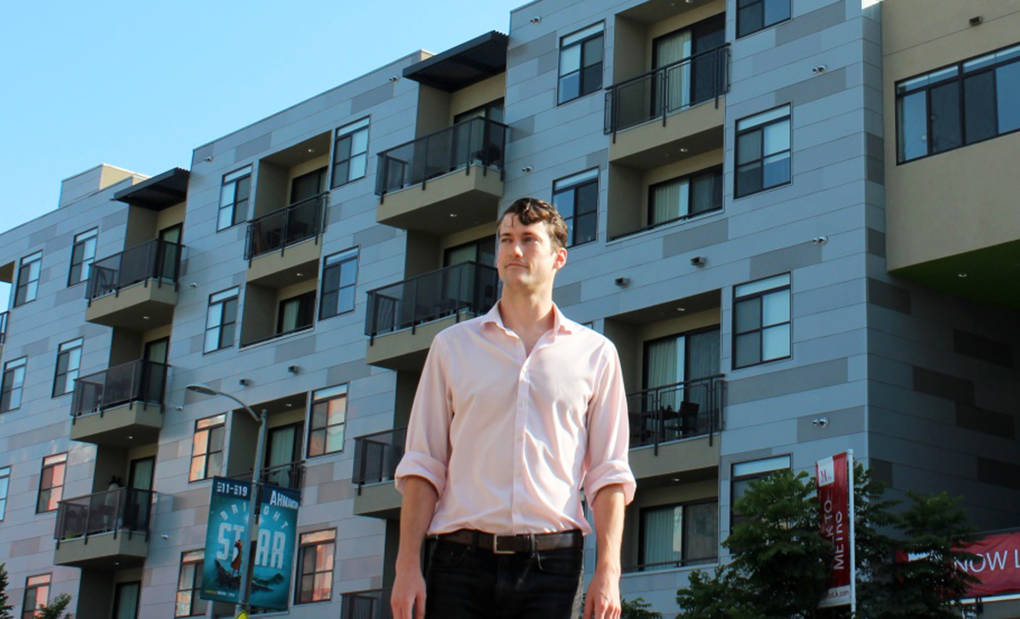 Brent Gaisford, 27, leads Abundant Housing L.A., one of the area's YIMBY organizations. Behind him is the M Lofts in Palms, the kind of development he said L.A. should be building more of.