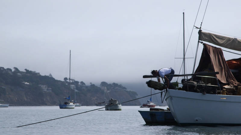 An anchor-out community member throws a buoy into Richardson Bay.