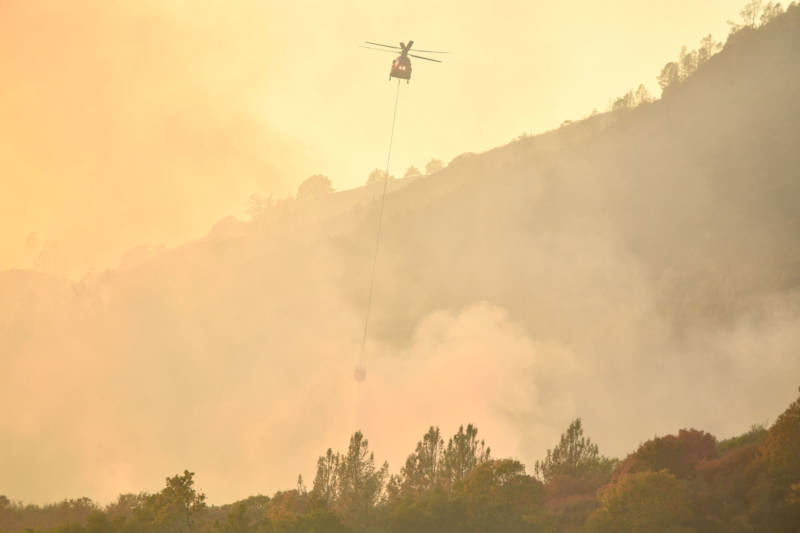 A helicopter drops water on flames in Calistoga on October 11, 2017.