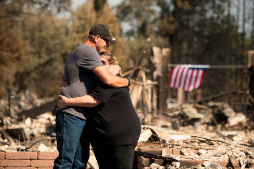 Charlie and Kate Higgins embrace in front of their burned home in Santa Rosa on Oct. 12, 2017.