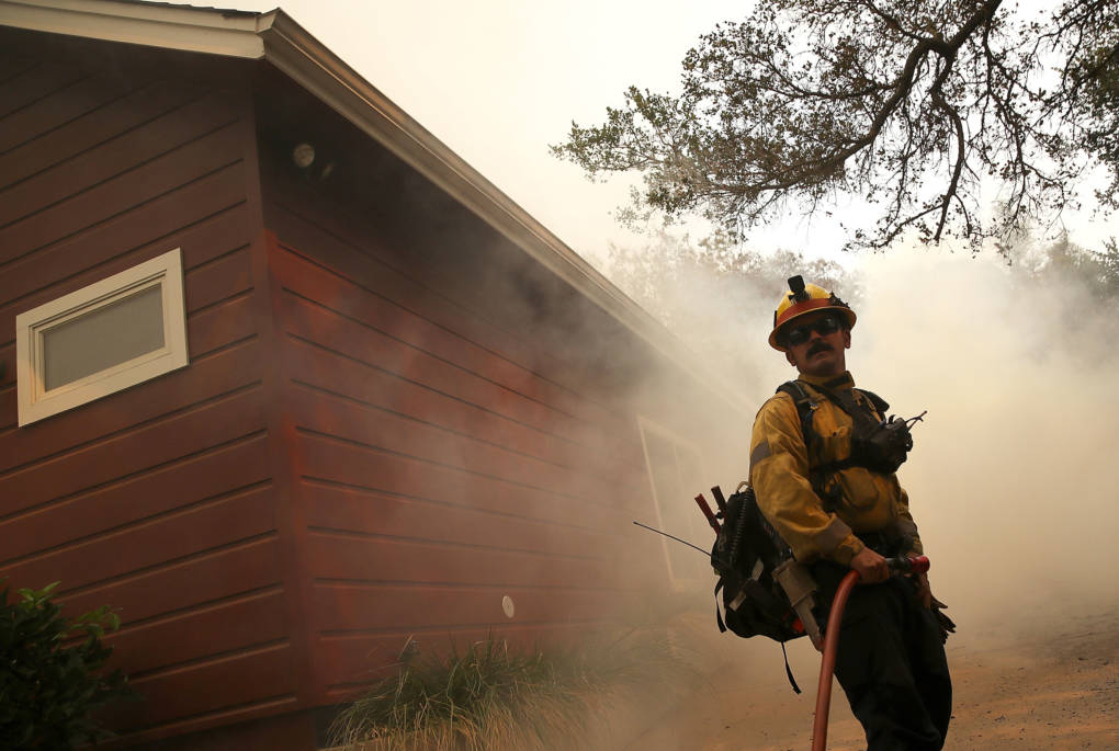 A Los Angeles County firefighter monitors approaching flames near a building as an out-of-control wildfire moves through the area on October 9, 2017 in Yountville, north of Napa.