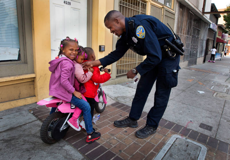 Officer Rodney Freeman passes out stickers on Third Street in the Bayview, where many black residents live. So many families have left the city due to its high cost of living that it now has a lower percentage of children than any other major U.S. city.