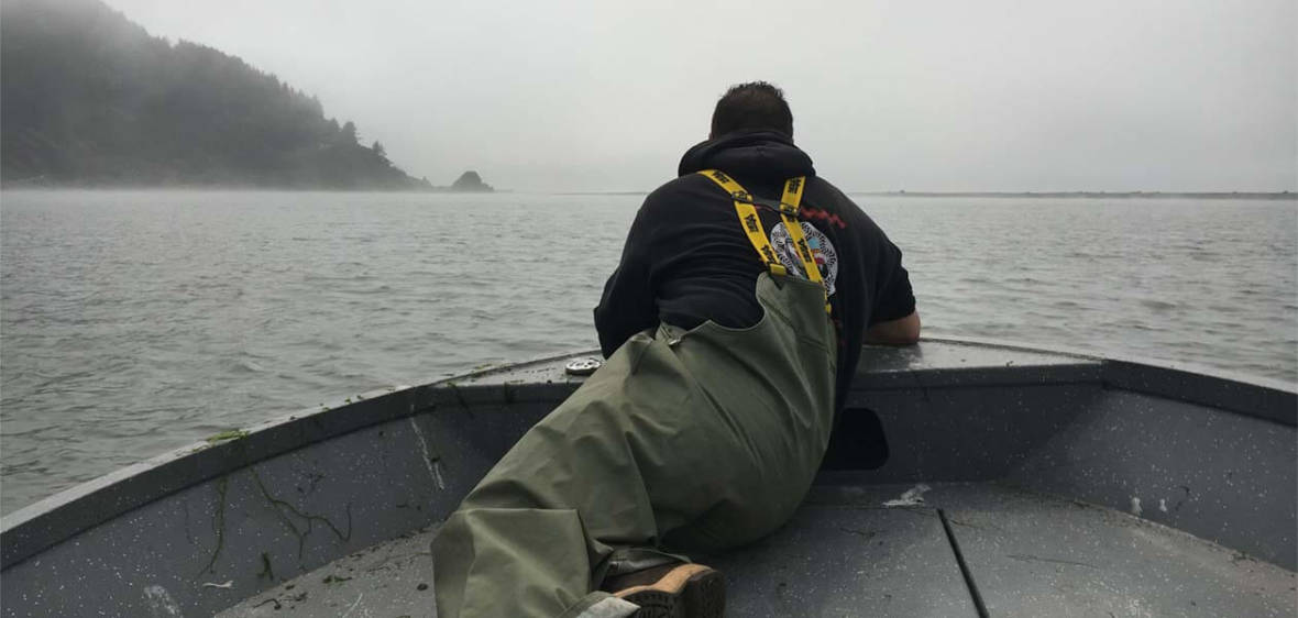 Jerome Nick Jr. peers over the bow while checking nets near the mouth of the Klamath River in California's far north.  Lisa Morehouse/KQED