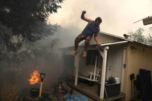 A resident rushes to save his home as an out-of-control wildfire moves through the area on October 9, 2017 in Glen Ellen.