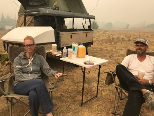Meg and Jeff Nyholm pitch a tent at the corner of Old Redwood Hwy. and Airport Blvd. They've been sleeping in it since evacuating their home on Monday morning.