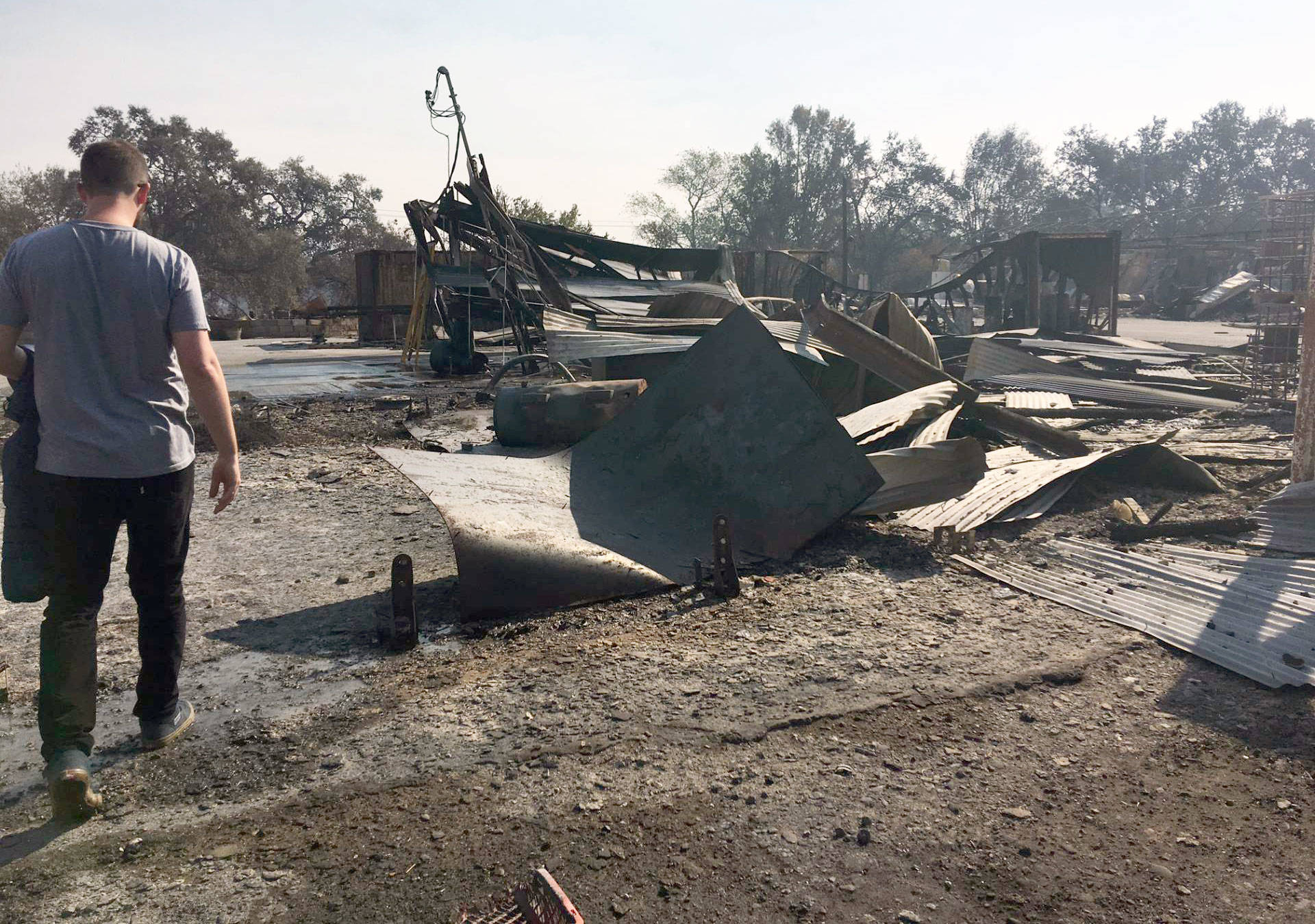 Ned Russell walks through the charred remains of his farm.