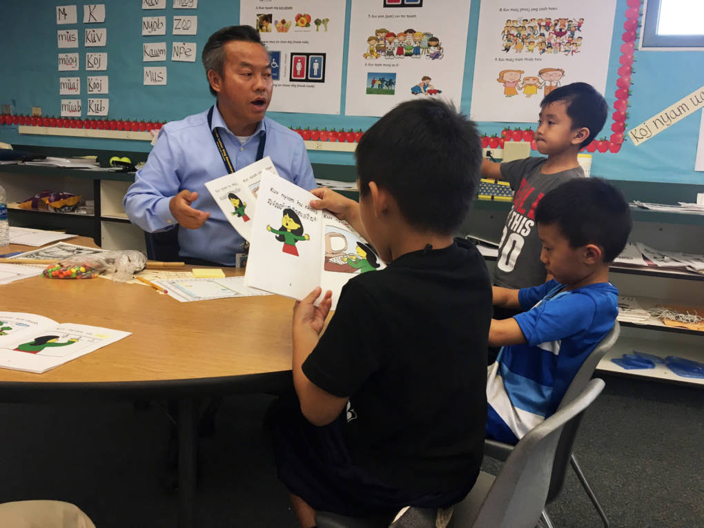 Teacher Thae Xiong reads students a book in Hmong.