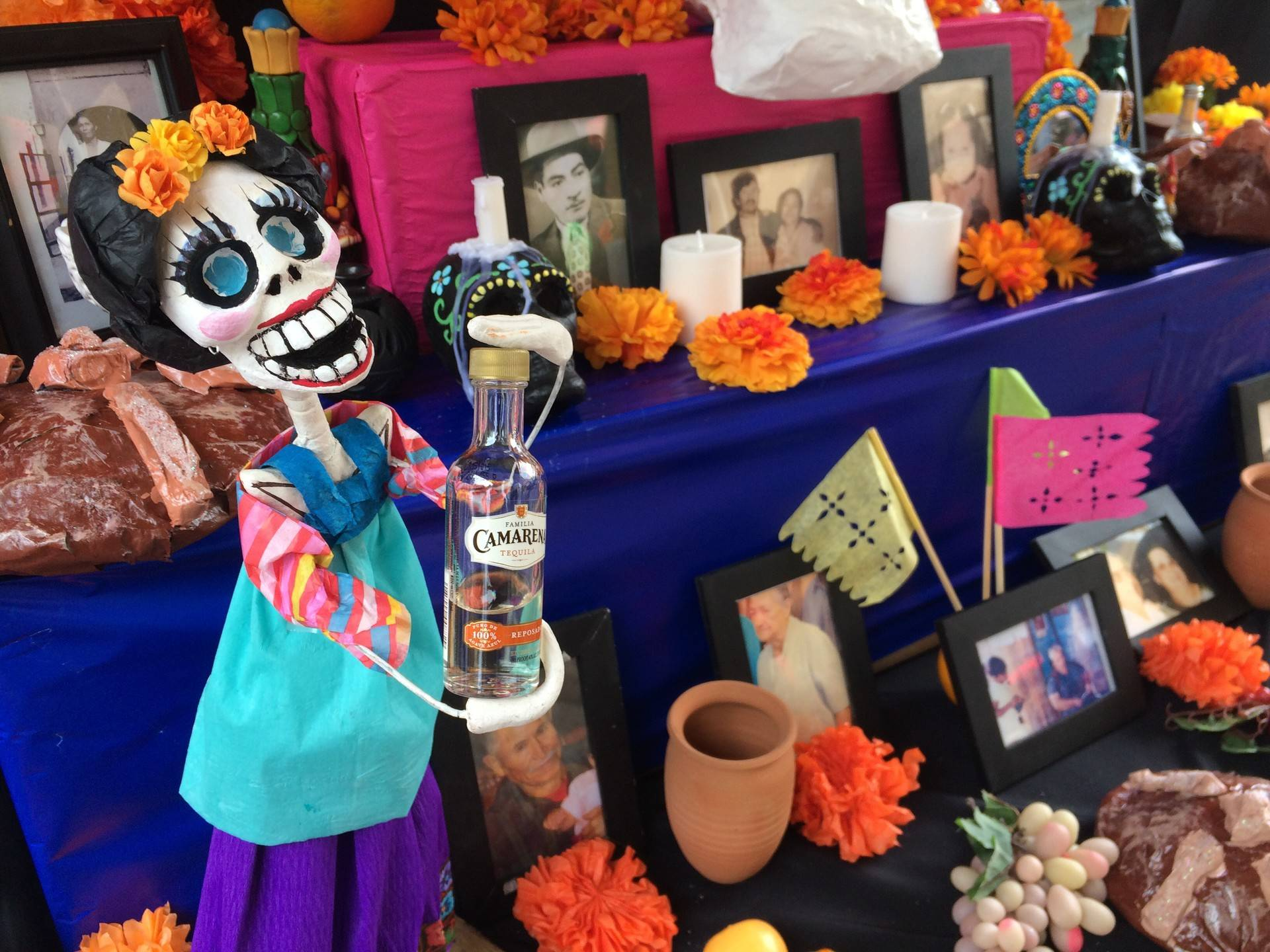 """Artist Andrea Luna adorned her altar with  """"Amor Eterna,"""" which depicts a calavera holding the favorite drink of deceased loved one. Tiffany Camhi/KQED"""