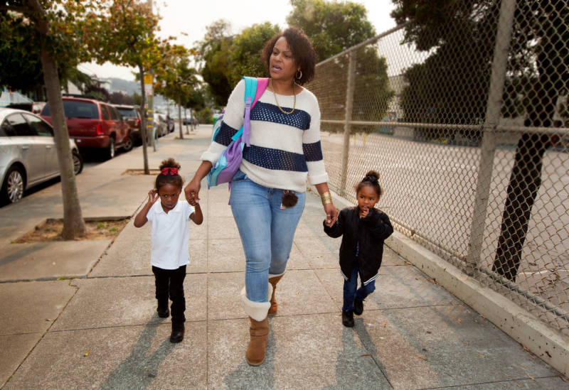 Raushanah Riles walks her twin nieces home from pre-school at Charles R. Drew College Preparatory Academy in the Bayview.