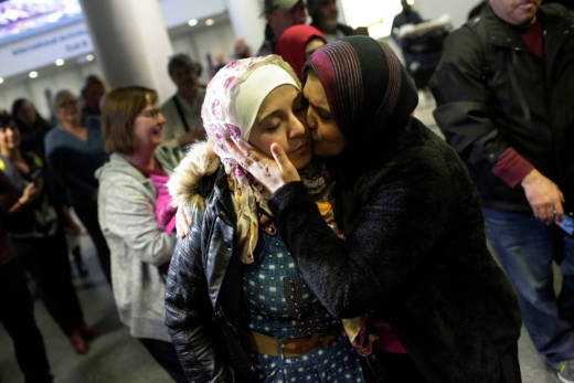 Syrian refugee Baraa Haj Khalaf (L), receives a kiss from her mother Fattoum Haj Khalaf as she arrives in the United States on February 7, 2017.
