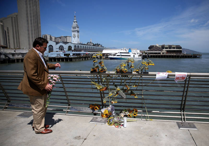 A well-wisher drops off flowers at the site where 32-year-old Kathryn Steinle was killed on Pier 14 in San Francisco.