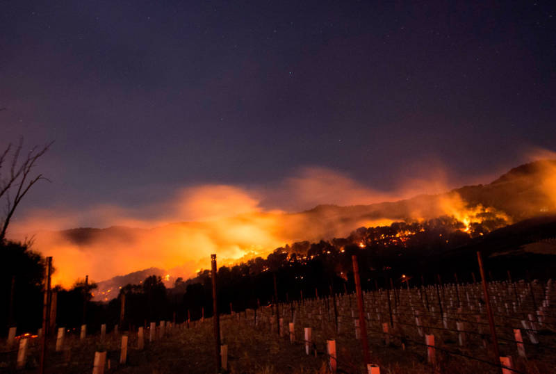 Fire glows on a hillside in Napa on October 9, 2017, as multiple wind-driven fires continue to whip through the region.