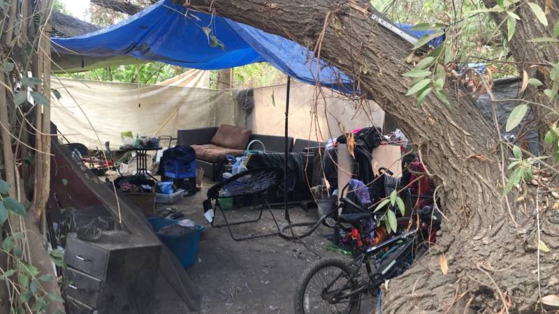 A bike, sofa and other belongings are stored in this makeshift shelter.