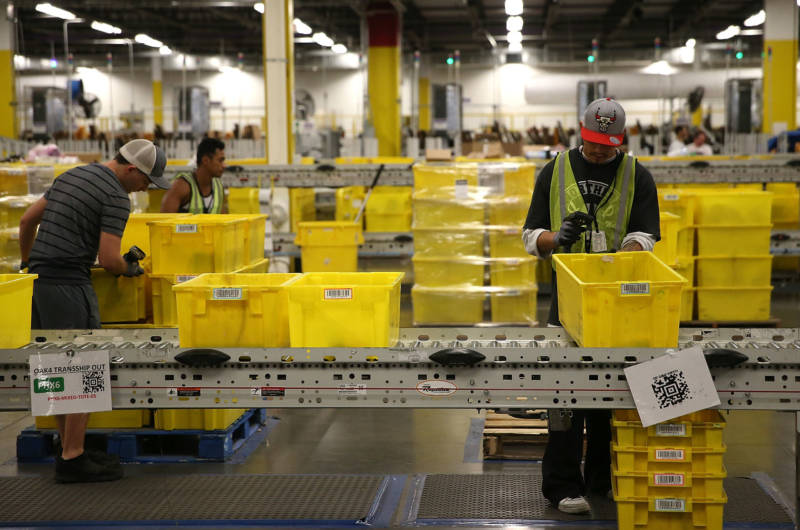 Workers pack orders at an Amazon fulfillment center in Tracy.