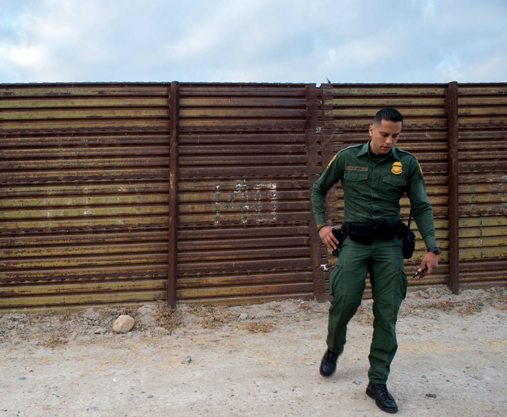 A U.S. Border Patrol agent stands next to the U.S.-Mexico border.
