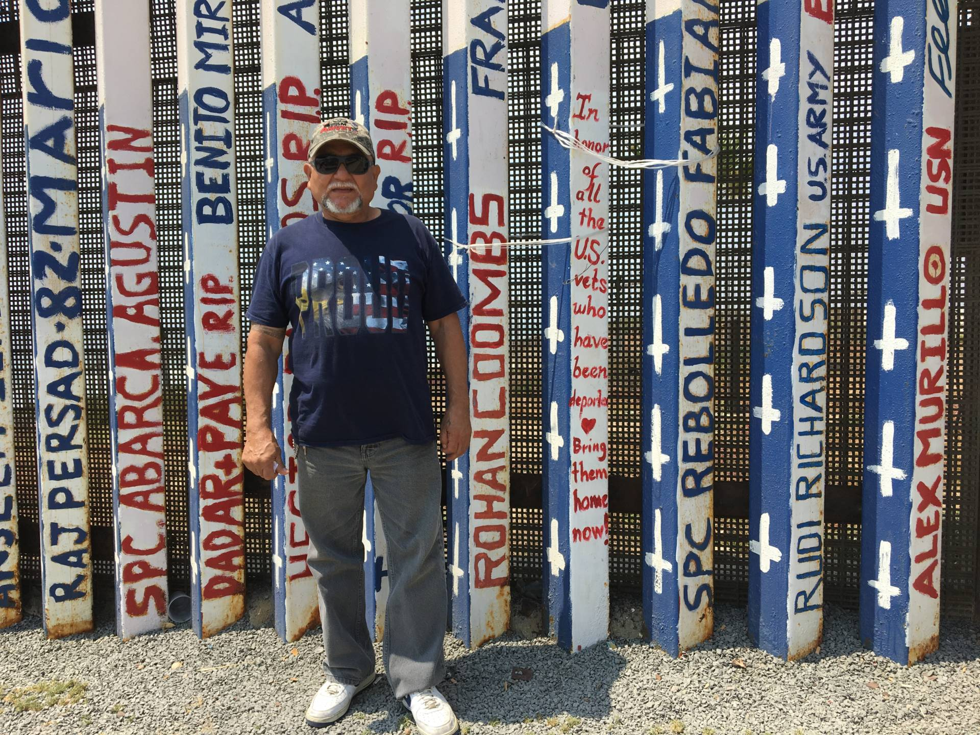 Jose Cardenas, 67, stands at U.S.-Mexico border fence in Tijuana that has been painted with the names of deported U.S. veterans. Cardenas was drafted into the U.S. Army in 1970, served seven years in the U.S. military and was deported in 2009 after a drug conviction.  Erika Aguilar/KQED News