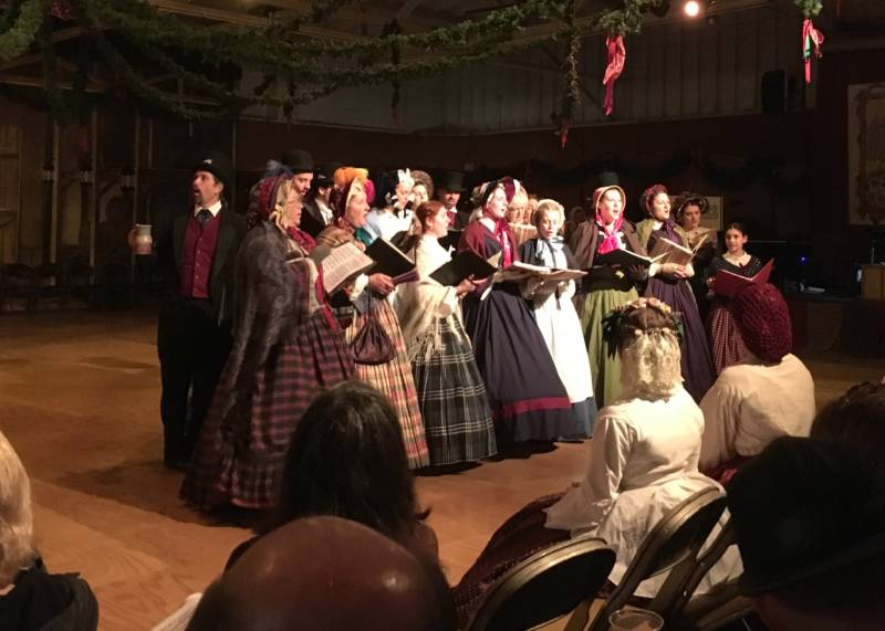 Carol singers dressed in head-to-toe Victorian attire spread holiday cheer as they sing through the halls of Cow Palace, which has been converted into the streets of Victorian London.