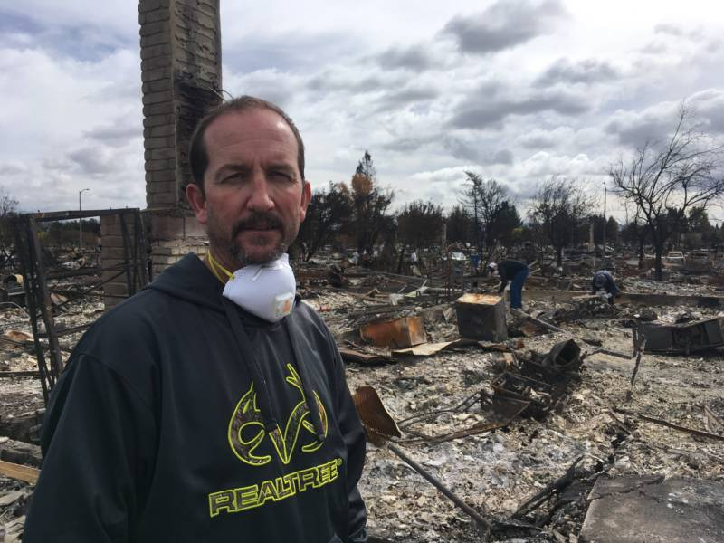 Brett Donnells in front of his burned homesite in Coffey Park the same day the insurance adjuster came to assess his losses.