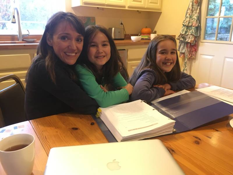 Carolynn Spezza sits at the kitchen table in her new home with her two daughters, a pile of insurance paperwork on the table in front of them.
