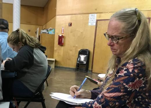 Katrina Frey takes notes at a town meeting in Redwood Valley, where officials talk about debris clean up and housing needs after the wildfires.