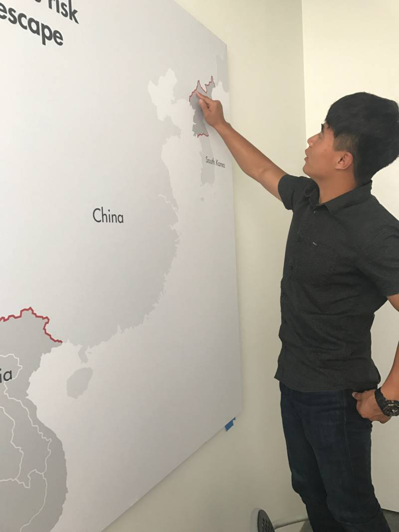 """In the offices of LiNK (Liberty in North Korea), Cheol """"Charlie"""" Ryu points at the approximate spot, on the Chinese-North Korean border, where he crossed the Yalu River to defect."""