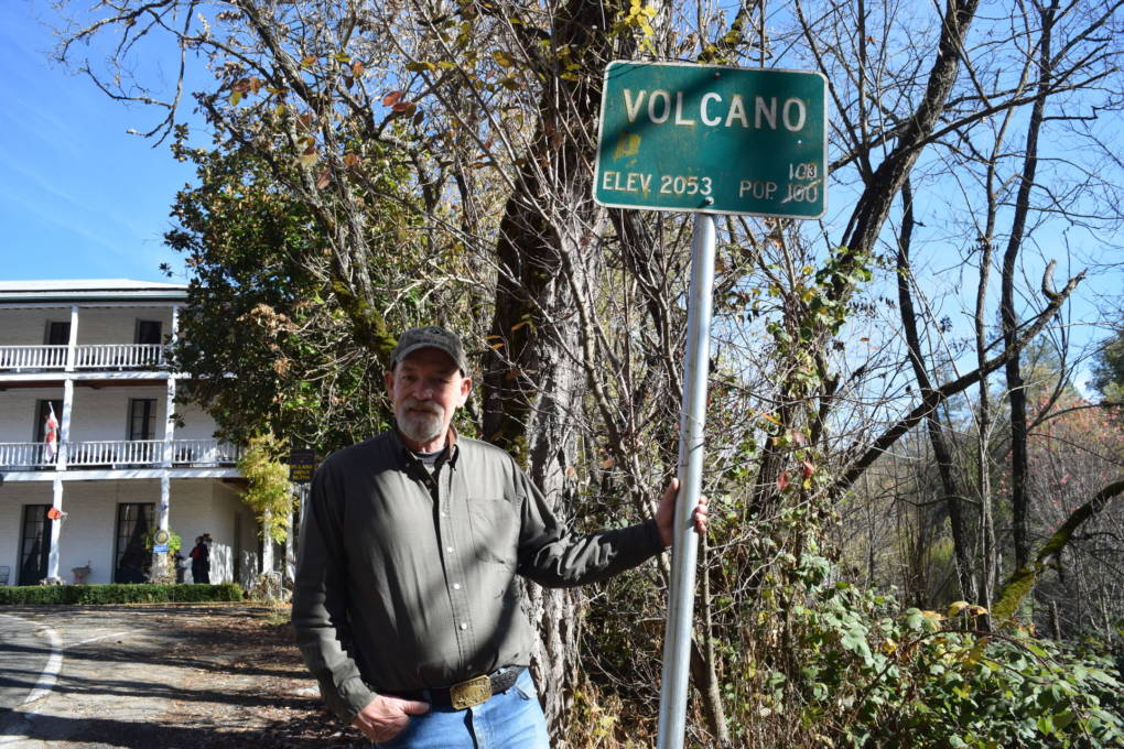 John Hemstreet stands by the sign at the entrance to Volcano, in front of the George Hotel.