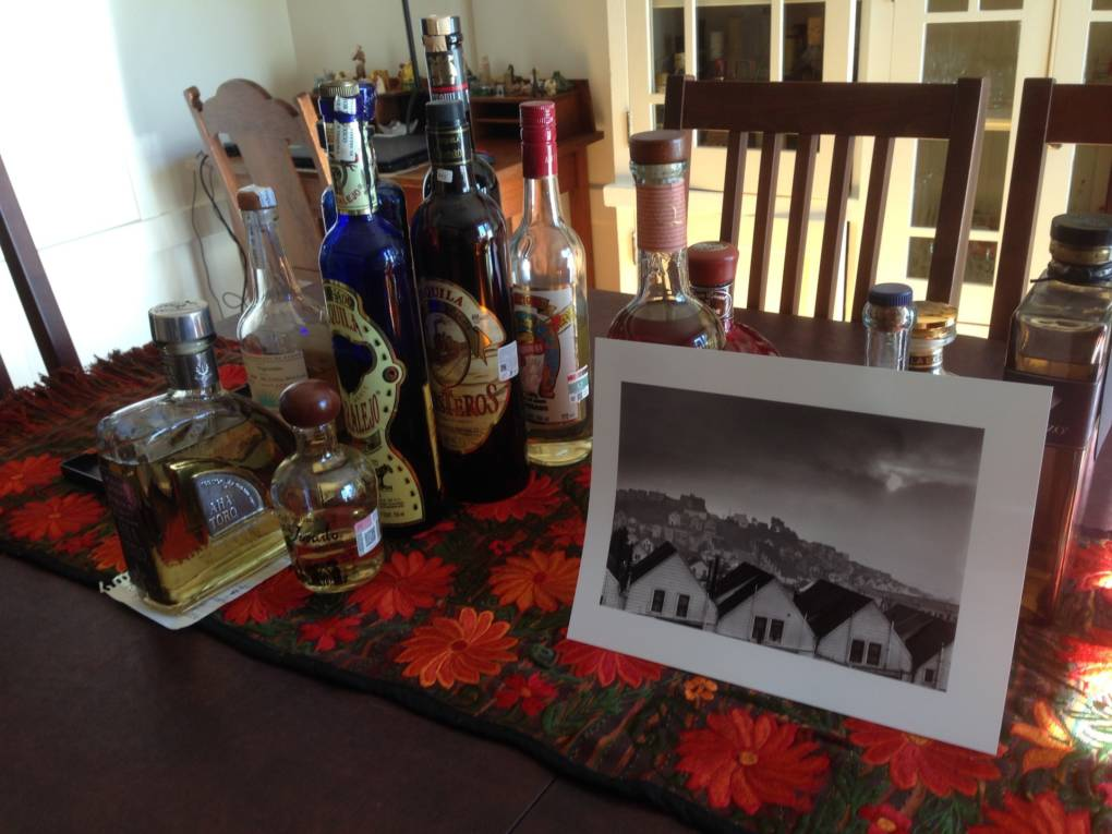 "Fred Lyon gave Robert Aranda Jr. a digital print of his ""Houses on the Hills"" photograph. It is temporarily keeping company with tequila bottles on Aranda's dining room table in the Noe Valley neighborhood of San Francisco."