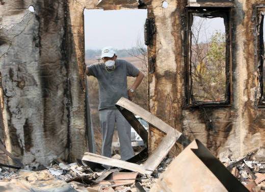 A man discovers his home destroyed in Rancho Bernardo, North San Diego on Oct. 25, 2007. The California Public Utilities Commissions has voted to have San Diego utility shareholders, not ratepayers, pay $379 million in costs from three 2007 deadly blazes ignited by power lines.