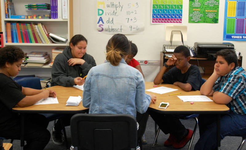 Special education instructional aide Jocelyn Ramirez (middle) works with students in small groups at Oak Ridge Elementary School in the Sacramento Unified School District.