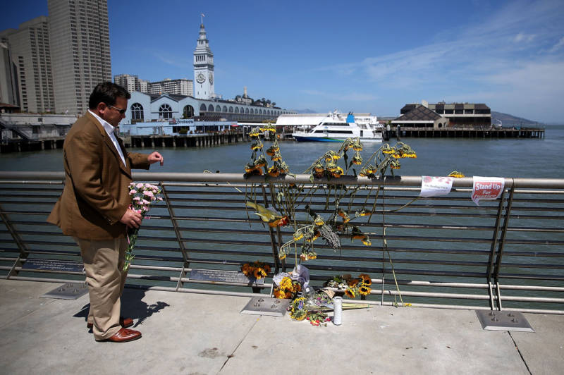 A well-wisher drops off flowers at the site where 32-year-old Kathryn Steinle was killed on July 6, 2015 in San Francisco.
