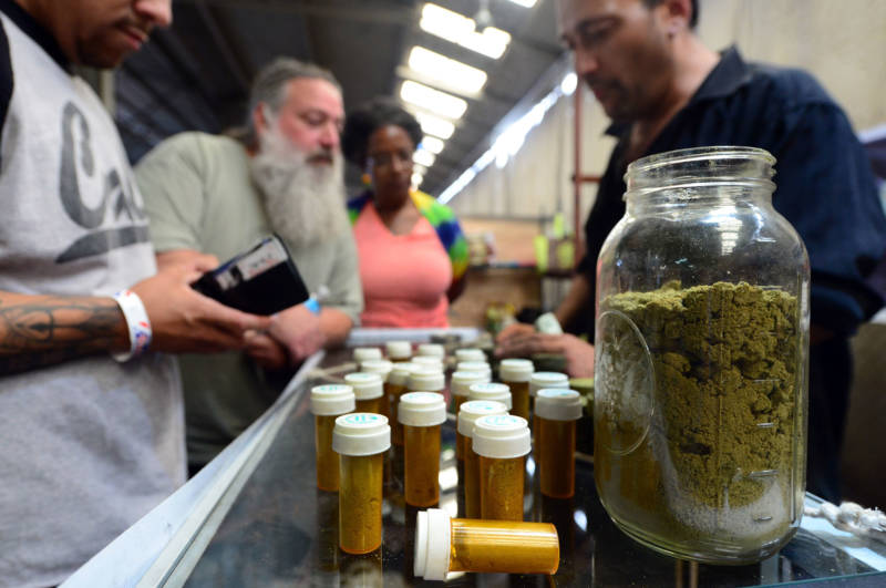 A customer prepares to buy marijuana from a cannabis farmers market in L.A.