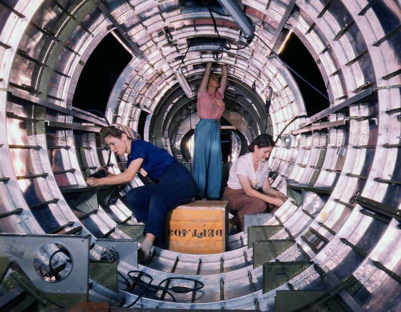 WWII woman workers assemble fuselage of Douglas airplane