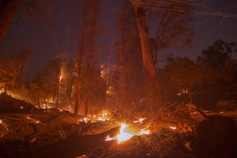 A strong wind blows embers from smoldering trees at the Thomas Fire on December 16, 2017 in Montecito, California.