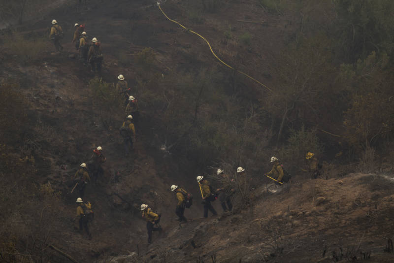 A Hot Shot crew marches through a canyon between homes to fight the Thomas Fire on December 16, 2017 in Montecito, California.
