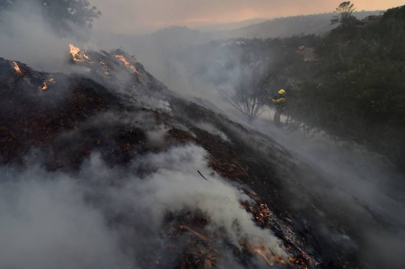 A firefighter puts out hotspots on a smoldering hillside in Montecito, California as strong winds blow smoke and embers inland on December 16, 2017 at the Thomas Fire.