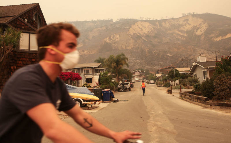 A man bicycles past bluffs burned in the Thomas Fire on December 7, 2017 in La Conchita.