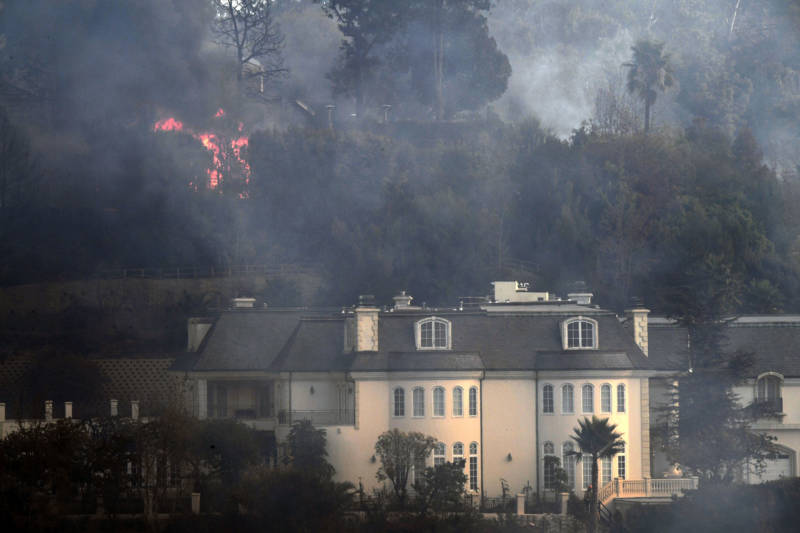 Flames burn behind a Bel Air mansion threatened by the Skirball Fire in west Los Angeles on Dec. 6, 2017.