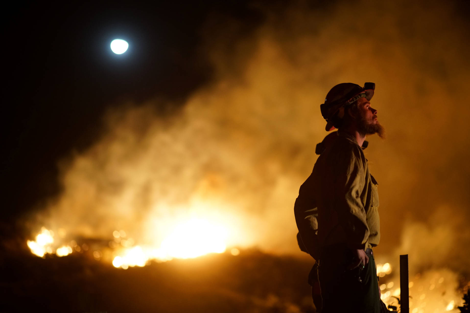 A firefighter watches the fire line at the Lilac fire in Bonsall, California on Dec. 7, 2017. Local emergency officials warned of powerful winds on Dec. 7 that will feed wildfires raging in Los Angeles, threatening multi-million dollar mansions with blazes that have already forced more than 200,000 people to flee. Sandy Huffaker/AFP/Getty Images