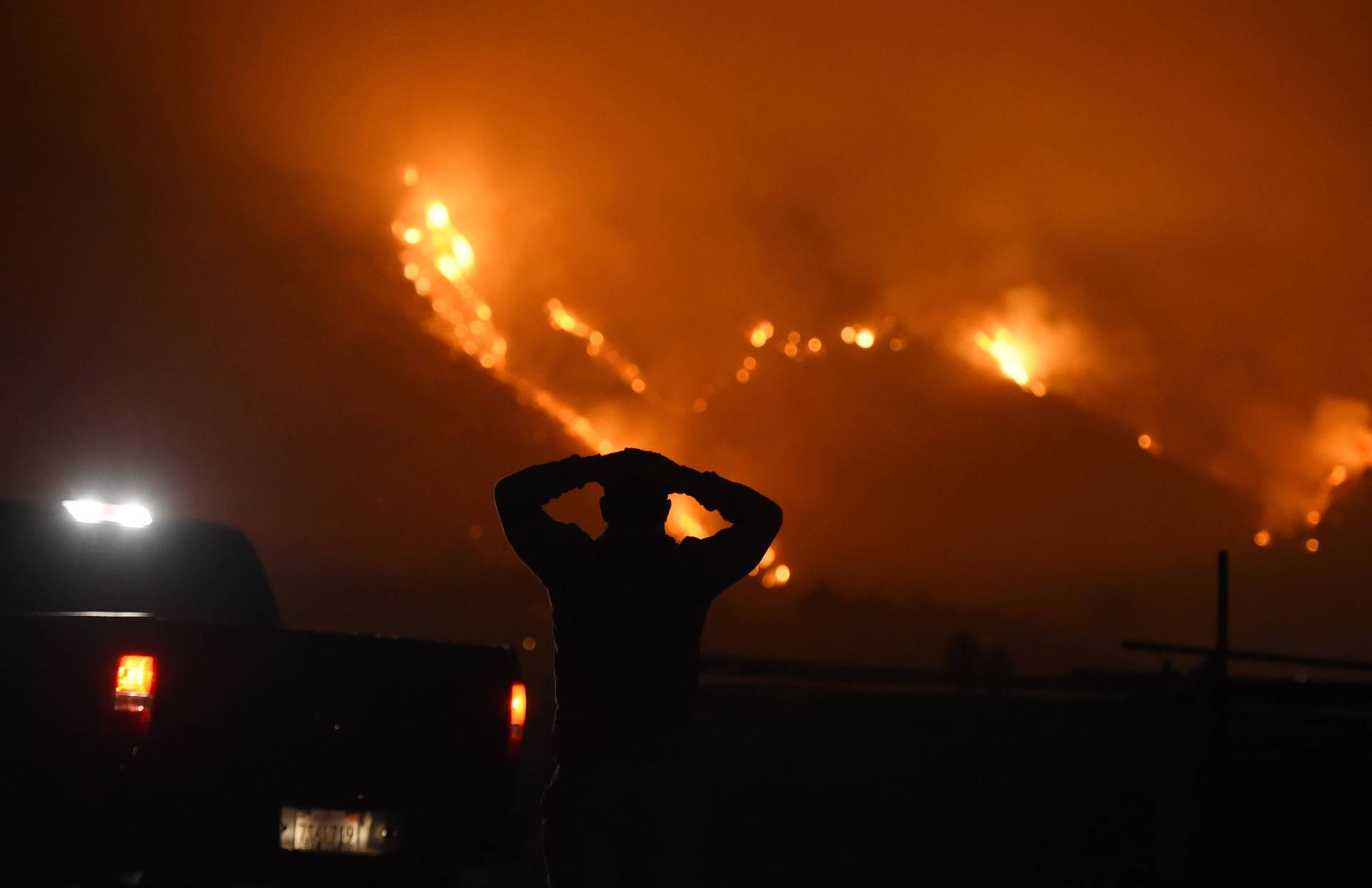 A man watches the Thomas Fire in the hills above Carpinteria on Dec. 11, 2017. The fire, burning in California's Ventura and Santa Barbara counties, has consumed more than 230,000 acres over the past week, making it the fifth-largest fire in state history. Robyn Beck/AFP/Getty Images