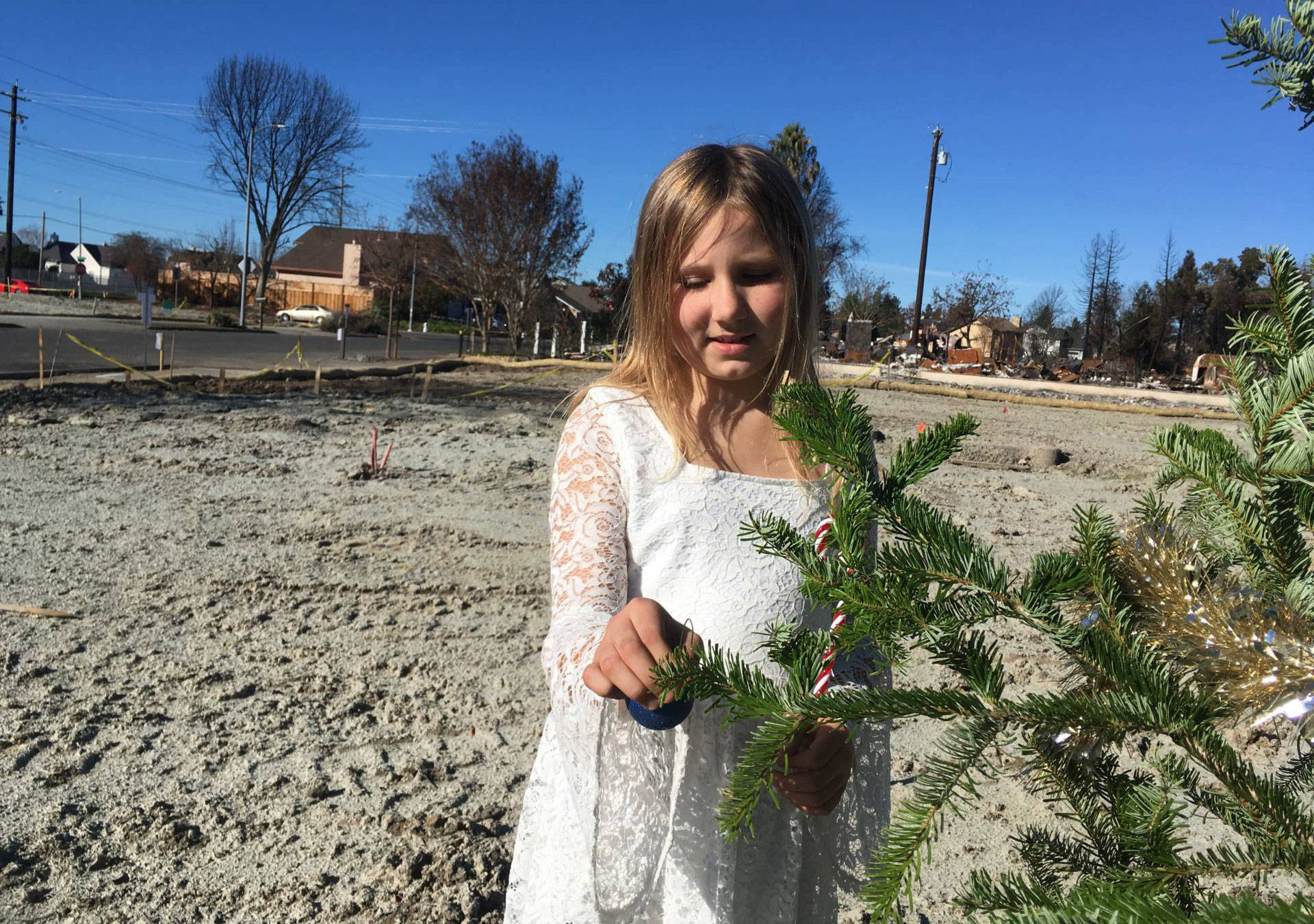 Lilly Pell decorates a Christmas tree where the front door of her house used to be. It was destroyed in the North Bay wildfires.