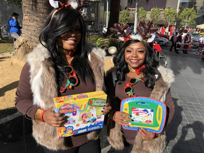 "Mattia Edwards and Jessica Gaines show off the toys they plan to donate at San Francisco's Union Square for SantaCon 2017. Edwards called the event, ""Christmas for adults."""