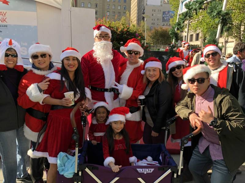 Philip Jang (center with beard), Jenny Jang (to his left) and their daughters Jasmine and Tiffany Jang (in the cart) celebrate SantaCon 2017 with friends at San Francisco's Union Square. Philip says the girls already had their Santa outfits but he and Jenny had to buy new ones for the event.
