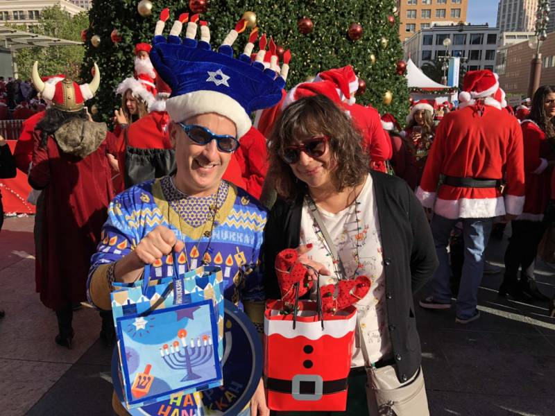 Andrew and Jennifer Fischer bring their mixed-religion marriage to SantaCon 2017 at San Francisco's Union Square. The Fischers say they've been going to the event on and off for years and love seeing the creativity of San Francisco on display. Andrew hands out dreidels and chocolate Hanukkah gelt while Jennifer hands out Christmas treats.