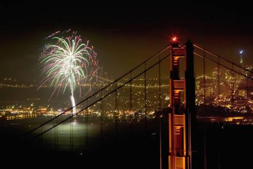 Fireworks light up the Golden Gate Bridge and San Francisco Bay.