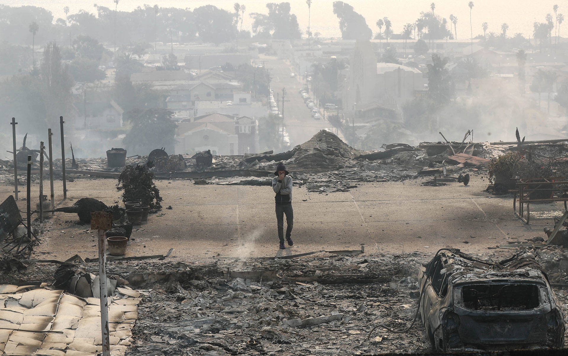 A resident walks in the remains of an apartment complex destroyed by the Thomas Fire in a residential neighborhood on Dec. 5, 2017 in Ventura.
