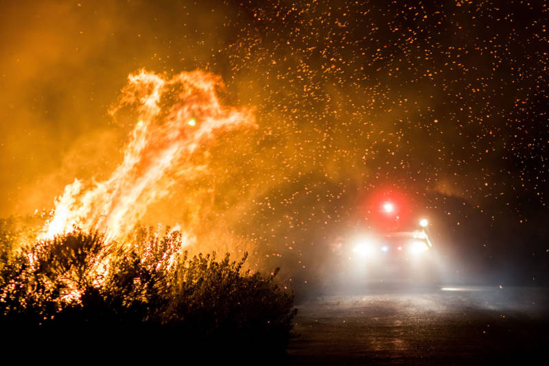 Firefighters battle the Thomas Fire as it burns past the 101 Freeway towards the Pacific Coast Highway in Ventura on Dec. 7, 2017.
